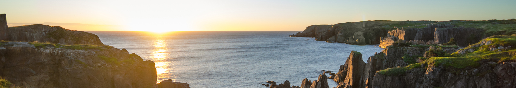 panoramic view of cliffs overlooking the ocean with a sunrise in the background
