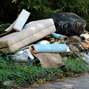 pile of used items including a mattress and mat thrown on the side of the road
