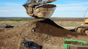 compost with an excavator bucket digging into it