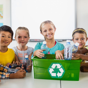 group of kids sitting around a recycling bin