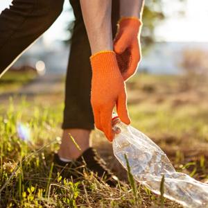 person outside wearing orange gloves picking up litter